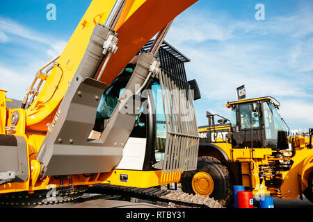PARIS, FRANCE - SEP 5, 2014: Yellow Liebherr excavator and Cat tractor parked on a street near the construction site on a sunny day - Stock Photo
