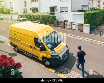 PARIS, FRANCE - JUN 23, 2017: Courier walking toward La Poste yellow delivery van for the delivery on time package parcel - aerial view - Stock Photo