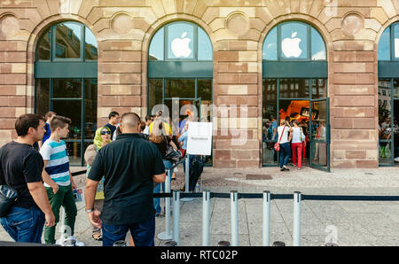 STRASBOURG, FRANCE - SEP 20, 2014: Customers waiting in line to pick-up their new reserved iPhone 7 from the Apple Store computer store selling iPad, Apple Watch and iMac MacBook pro computers - Stock Photo