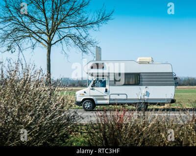 Dortmund, Germany - Feb 24, 2018: Side view of vintage RV camper van driving toward vacation destination on a warm clear sunny morning in German autobahn