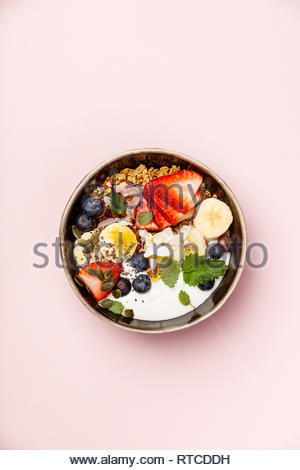Healthy vegetarian breakfast- Oat granola with fresh berries, banana, yogurt, maple syrup, seeds and mint leaves on pink background, flat lay, top vie - Stock Photo