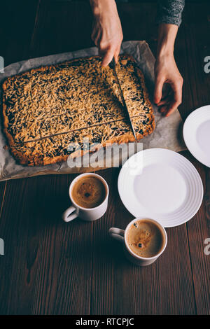 Top view woman's hands cutting freshly baked cookies next to two cups of coffee and plates on brown wooden table. - Stock Photo