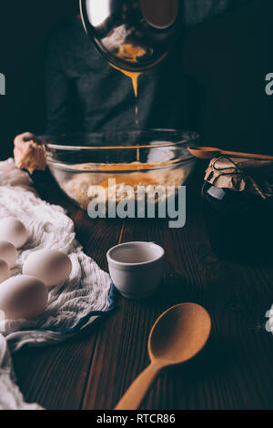Cropped image of woman at table cooking pie dough, pouring yolks into flour with butter in large transparent bowl among utensils and ingredients for h - Stock Photo