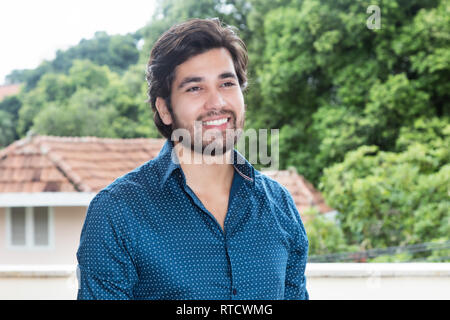 Laughing hispanic hipster man with beard outdoors with copy space - Stock Photo
