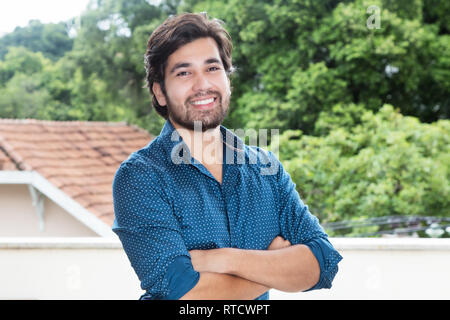Modern hispanic hipster man with beard outdoors with copy space - Stock Photo
