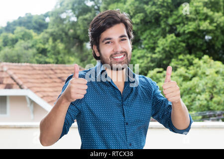 Hispanic hipster man with beard showing thumbs up outdoors with copy space - Stock Photo