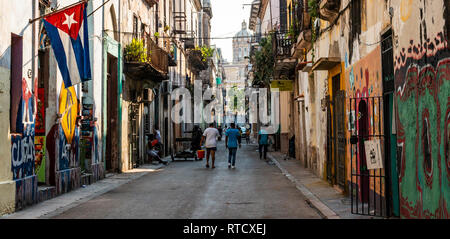 Havana, Cuba - 25 July 2018: View of a street in old Havana with people walking, the capitol building in view, a Cuban flag and graffiti on the walls. - Stock Photo