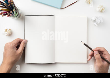 Design concept - Top view of man's two hand hold high grade brown notebook and pen isolated with crumpled paper on white background for mockup - Stock Photo