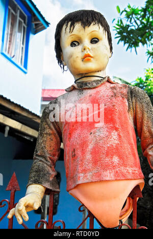 One dirty colorful plastic doll without legs trapped on a garden fence. It is a low-angle view with a house in the background, seen in the Philippines - Stock Photo