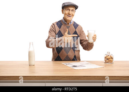 Senior man holding a glass of milk and pointing at the glass behind a wooden counter isolated on white background - Stock Photo