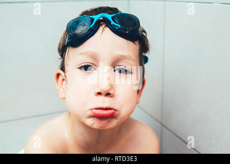 Child bathing in his bathroom with diving glasses making funny gestures. - Stock Photo