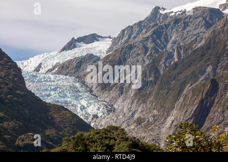 Franz Josef Glacier high in the mountains slowly coming down the vally New Zealand South Island - Stock Photo