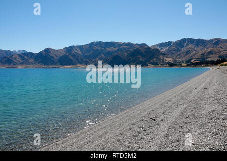 Beautiful Lake Hawea pebble beach with driftwood in summer blue sky clear water pebbles rocks New Zealand South Island - Stock Photo