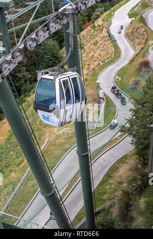Skyline gondola car, tower and cable over the luge on Ben Lomond mountain New Zealand South Island - Stock Photo
