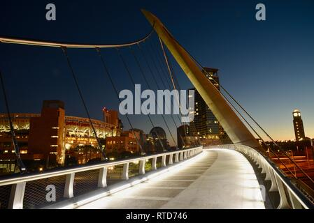 The iconic, modern 500-feet long Harbor Drive Pedestrian Bridge at sunrise, connects Petco Park to San Diego Bay and Convention Center, San Diego, USA - Stock Photo