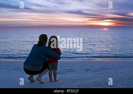 A mother and child watch the sun set over the Gulf of Mexico on Anna Maria Island, Florida, USA. - Stock Photo
