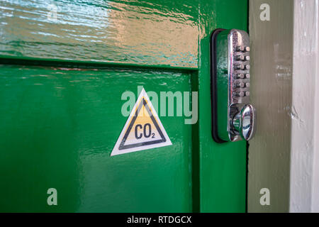 CO2 triangle warning sign and Digital Keypad Door Lock on an Old fashioned green wood door at Doncaster Station, England - Stock Photo