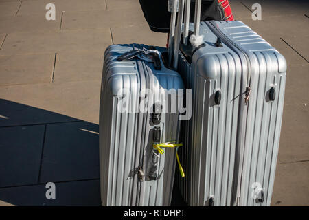 Young woman pulls her two Manoukian Luggage Set Aluminum cases out of Kings Cross Railway Station, London, England - Stock Photo