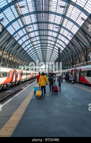 Arriving off a train passengers walking along a platform at Kings Cross Train Station, London, England - Stock Photo