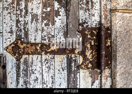 Detailed close-up of rusty old hinge on a door with peeling paint - Stock Photo