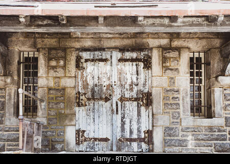 Worn door with peeling paint on abandoned stone building - Stock Photo
