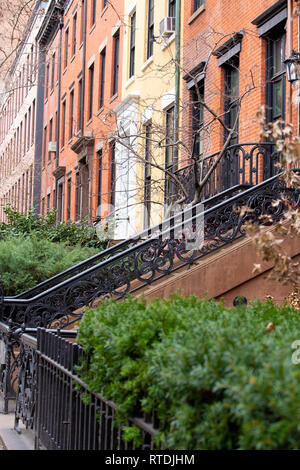 View of colorful apartment buildings and brownstones along pretty street in New York City. - Stock Photo