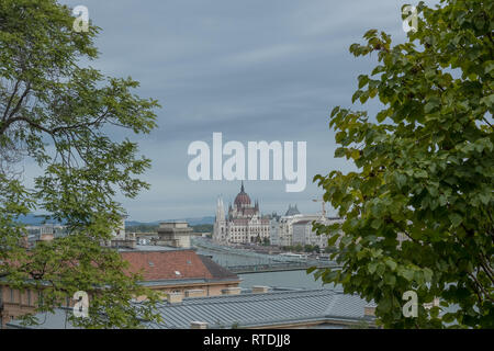 Framed by trees on both sides, looking across Danube from Buda to Hungarian Parliament in Pest, Budapest, Hungary - Stock Photo