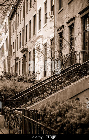 View of apartment buildings and brownstones along pretty street in New York City with sepia tone - Stock Photo