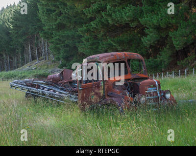 Abandoned derelict rusty,  Bedford truck, in long grass, Endeans Mill, Waimiha, Ongarue, King Country, New Zealand - Stock Photo