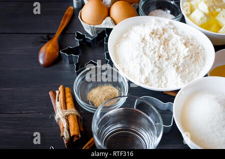 Set of ingredients for cooking festive Christmas gingerbread cookies - butter, flour, sugar, eggs, spices with  sugar decor, icing, forms for biscuits