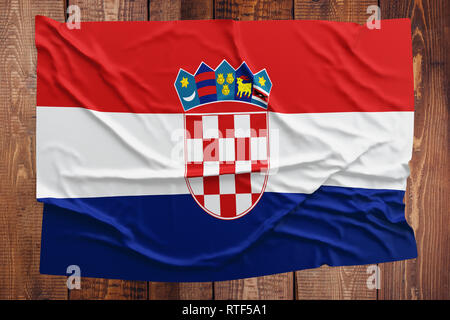 Flag of Croatia on a wooden table background. Wrinkled Croatian flag top view. - Stock Photo