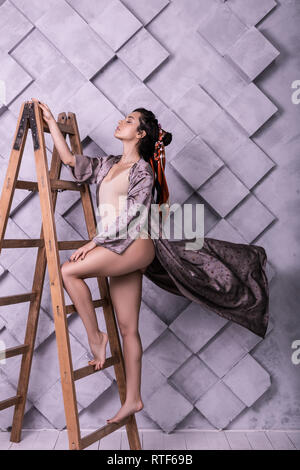 Slim graceful young sylph professionally posing during work in studio - Stock Photo