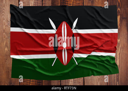 Flag of Kenya on a wooden table background. Wrinkled Kenyan flag top view. - Stock Photo