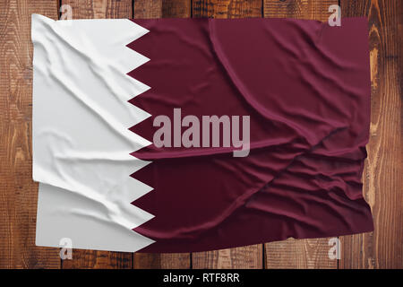 Flag of Qatar on a wooden table background. Wrinkled Qatari flag top view. - Stock Photo