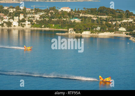 TWO CANADAIR CL-415 REFILLING IN THE SHELTERED BAY OF VILLEFRANCHE-SUR-MER TO COMBAT A NEARBY BRUSHFIRE. Saint-Jean Cap Ferrat, French Riviera, France. - Stock Photo