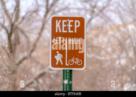 Keep Left Keep Right sign against trees and snow. Close up view of a road sign with snowy trees in the background. It instructs pedestrians to Keep Le - Stock Photo