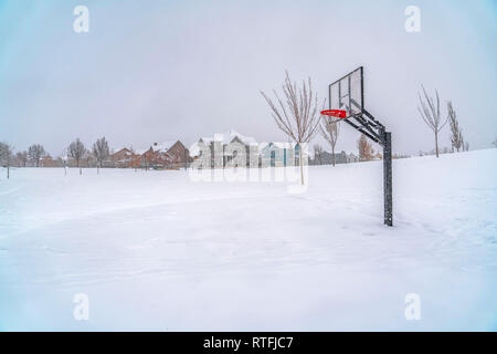 Outdoor basketball court covered with snow in Utah. Outdoor basketball court on a snow covered landscape in Daybreak, Utah during winter. Snowy trees  - Stock Photo