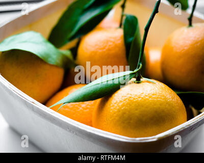 Some oranges with leaves in a basket, Orange Tangerines in a basket on a white background. - Stock Photo