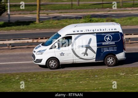 LHR Global Logistics van driving on the road. IATA accredited shipping agent. Transport company. Aviation graphic. Plane logo. London Heathrow - Stock Photo