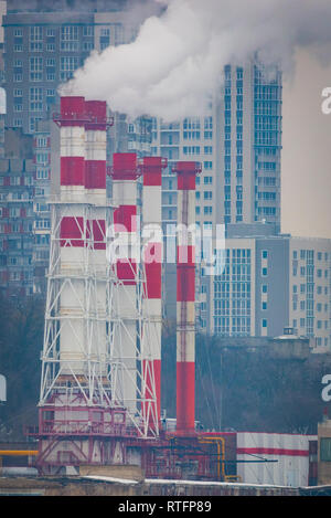 Air Pollution From Industrial Plants. Smoking industrial pipes. Red with white pipe. - Stock Photo