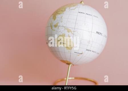 globe on peach colour show Australia and SE Asia - Stock Photo