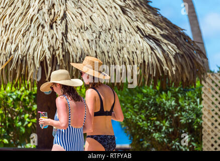 Two girls in bathing suits on the city beach, Rarotonga, Aitutaki, Cook Islands. With selective focus - Stock Photo