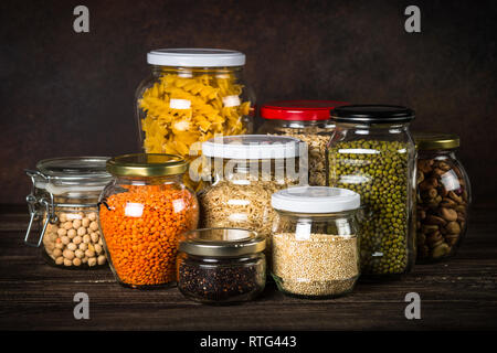 Cereals, Legumes, and beans in glass jars on  kitchen table.  - Stock Photo