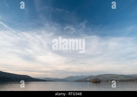 A wide shot of the head of Windermere from a boat, Wansfell Pike and the Fairfield Horseshoe are seen in the distance, Lake District, UK - Stock Photo