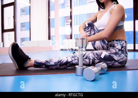 Dumbbells on the background of a blurred girl in the gym. - Stock Photo