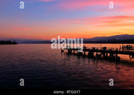 Blick Ÿber den ZŸrichsee bei Sonnenuntergang mit Bootsanleger auf die schneebedeckten Schweizer Alpen. - Stock Photo