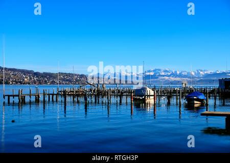 Blick Ÿber den ZŸrichsee mit Bootsanleger auf die schneebedeckten Schweizer Alpen. - Stock Photo