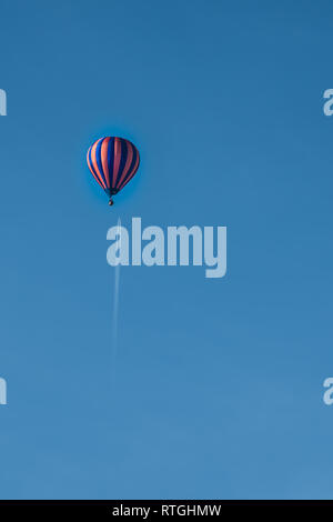 Hot Air Balloon flying under a Passenger Jet and con trail in a clear blue sky - Stock Photo