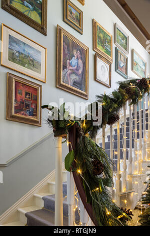 Framed artwork by Elizabeth Parsons in staircase with garland and lights - Stock Photo