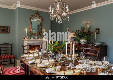 Mahogany dining table and Georgian sideboard with chairs upholstered in Regency stripe with English fireplace - Stock Photo